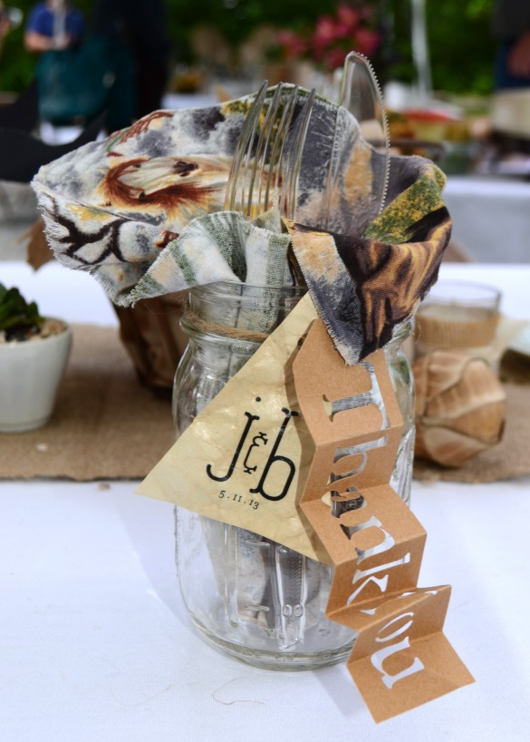 At each place setting, sat a mason jar containing a napkin and eating utensils. The mason jar also sports two hand made tags. One die cut tag that says thank you and another with the couple's custom monogram and the date on one side and on the other another little note that reads: